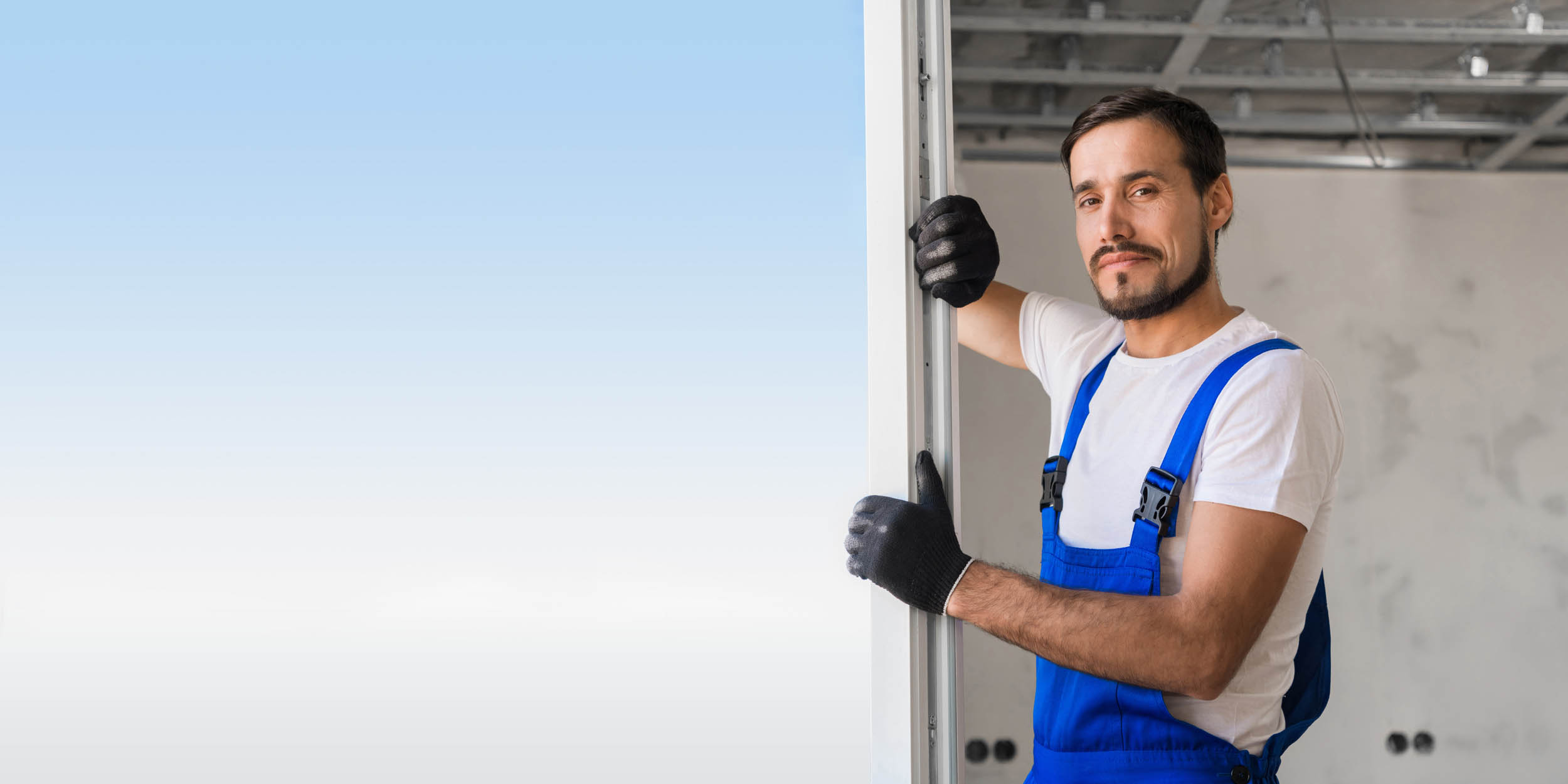 Adjuster in gloves installs the window in the apartment